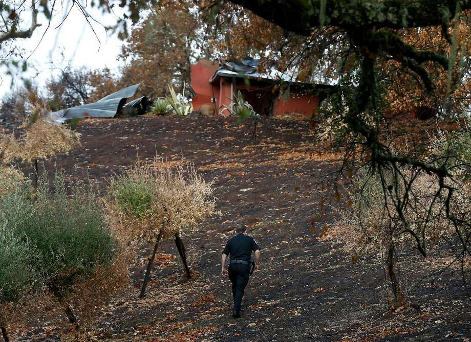 Security guard Joshua Antrim walks toward a damaged home on Bennett Lane near Calistoga, next door to the property at the center of the investigation into the start of the Tubbs Fire. Photo: Paul Chinn, The Chronicle