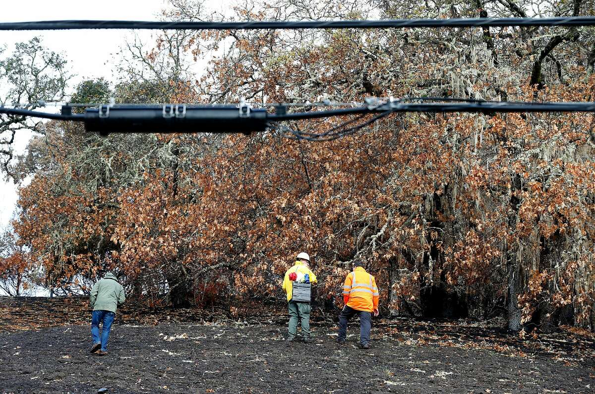 An inspection team walks on the charred property below power lines on Bennett Lane in Calistoga, Calif. on Friday, Nov. 10, 2017 where authorities believe the Tubbs Fire originated. PG&E filed legal papers suggesting that third party electrical equipment, not theirs, may have been the cause of last month's deadly Tubbs Fire.