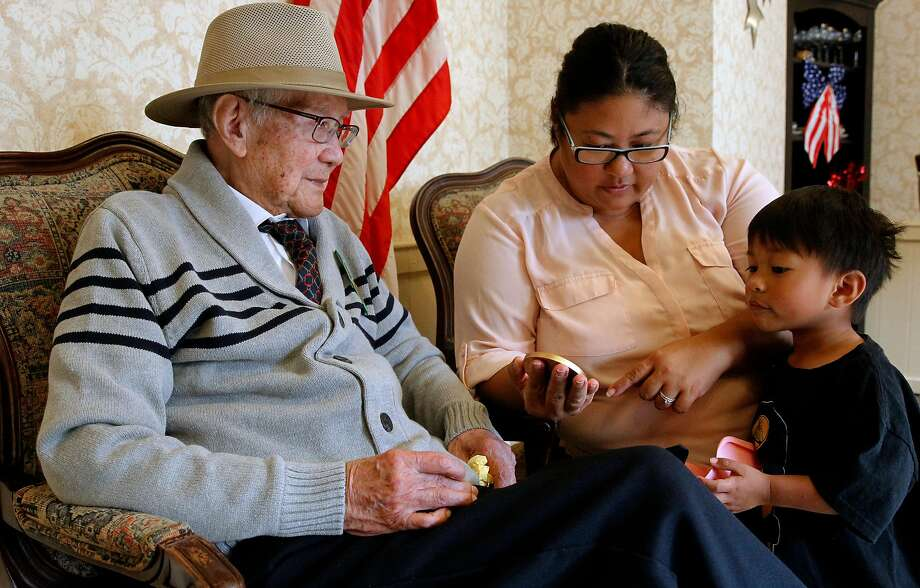 Amado Ante, granddaughter Juliet Rodriguez and great-grandson Rocco view the newly bestowed medal. Photo: Michael Macor, The Chronicle