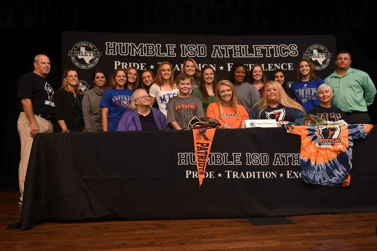 Alyssa Forrester, front row center, who plays softball for Kingwood Park High School, signs with the University of Texas at Tyler College during the Humble ISD Signing Day Ceremony at Charles Bender Performing Arts Center in Humble on Nov. 8, 2017. (Photo by Jerry Baker/Freelance)