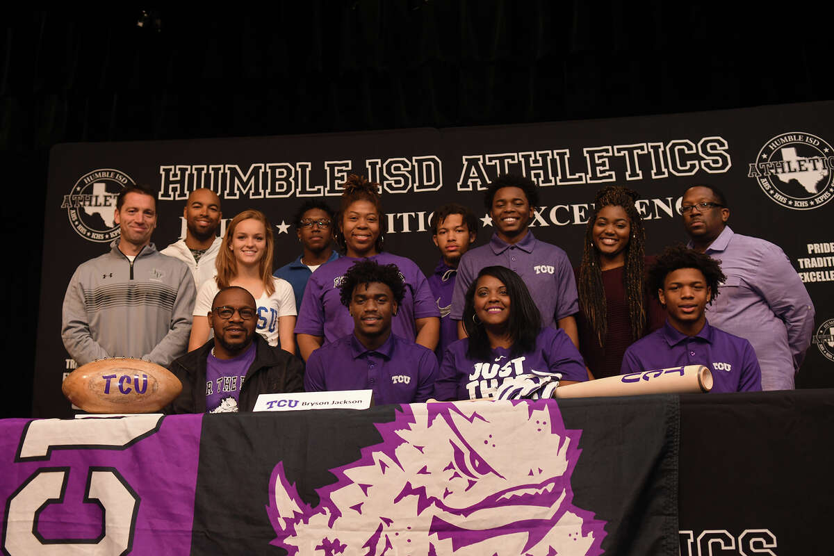 Bryson Jackson, front row center, who plays football for Kingwood Park High School, signs with Texas Christian University during the Humble ISD Signing Day Ceremony at Charles Bender Performing Arts Center in Humble on Nov. 8, 2017. (Photo by Jerry Baker/Freelance)