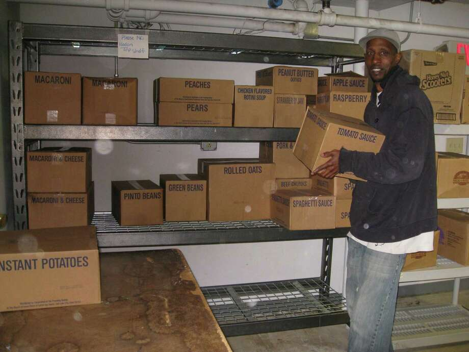 Daryl Fleming, residential monitor at the F.I.S.H. shelter in Torrington, assists in organizing the cases of food donated by the non-profit sponsorship of the Torrington Womans Club on behalf of the Church of Jesus Christ Latter Day Saints. Photo: Photo By Audree Peters /Not For Resale