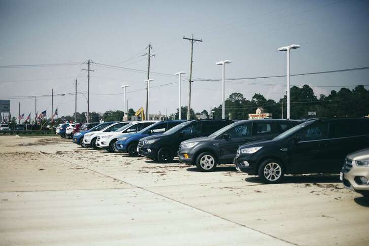 Water-damaged vehicles sit on the sales lot at McRee Ford in Dickinson, Texas.