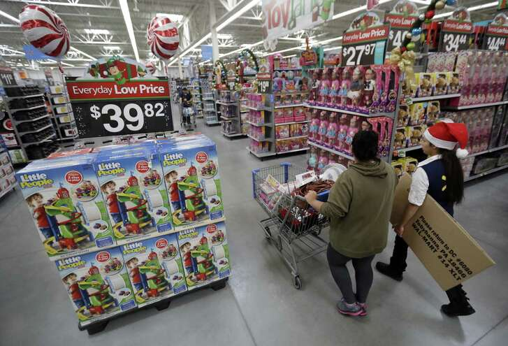In this Wednesday, Oct. 26, 2016, file photo, a shopper, left, walks with a store associate in the toy section at Walmart in Teterboro, N.J. Walmart hopes to tempt shoppers with online deals before Black Friday. Its beginning some online deals Thursday and plans to offer most of its Black Friday deals online starting at 12:01 a.m. on Thanksgiving.