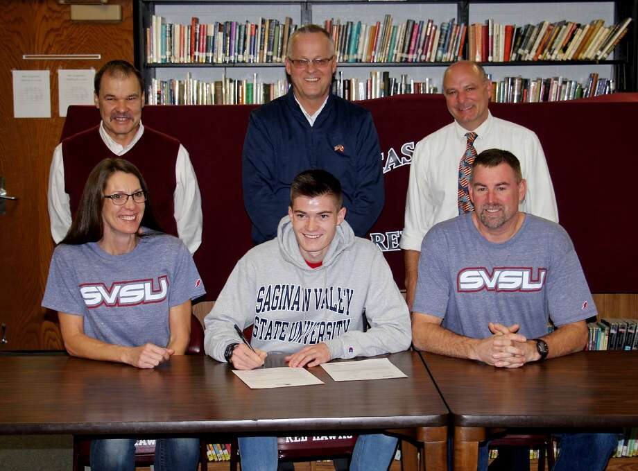 Cass City cross country/track standout CarLee Stimpfel (center) signs his letter of intent to continue his career at Saginaw Valley State University Friday in Cass City. He is joined in the front row by his parents Sloane and Tom. In the back row from left are Cass City athletic director Don Markel, superintendent Jeff Hartel and cross country/track coach Jon Zdrojewski. (Paul P. Adams/Huron Daily Tribune)