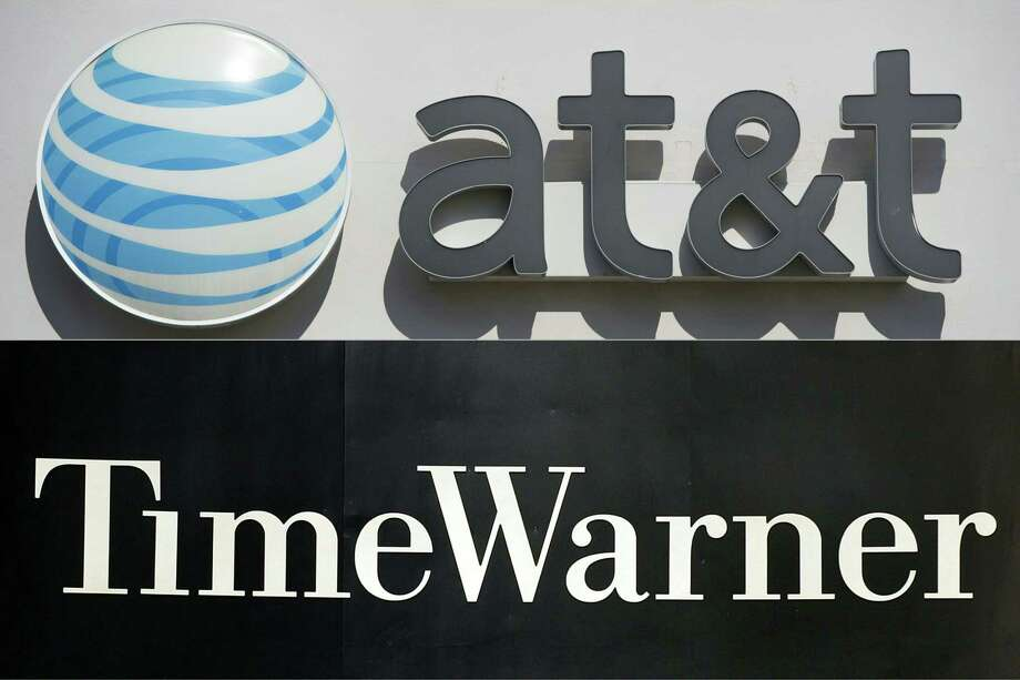 This file combination of pictures shows an AT&T cellphone store (TOP) in Springfield, Virginia, on October 23, 2014, and the Time Warner company logo on the front of the headquarters building, 24 November, 2003 in New York. Shares of Time Warner tumbled on November 2, 2017 following a report the Justice Department could move to block the proposed $85 billion takeover of the company by AT&T. The Justice Department is considering a lawsuit to block the megadeal, but has not made a final decision, the Wall Street Journal reported. The two sides are in settlement talks with the department, but they are not close to an agreement, the report said. Photo: SAUL LOEB /AFP /Getty Images / AFP or licensors