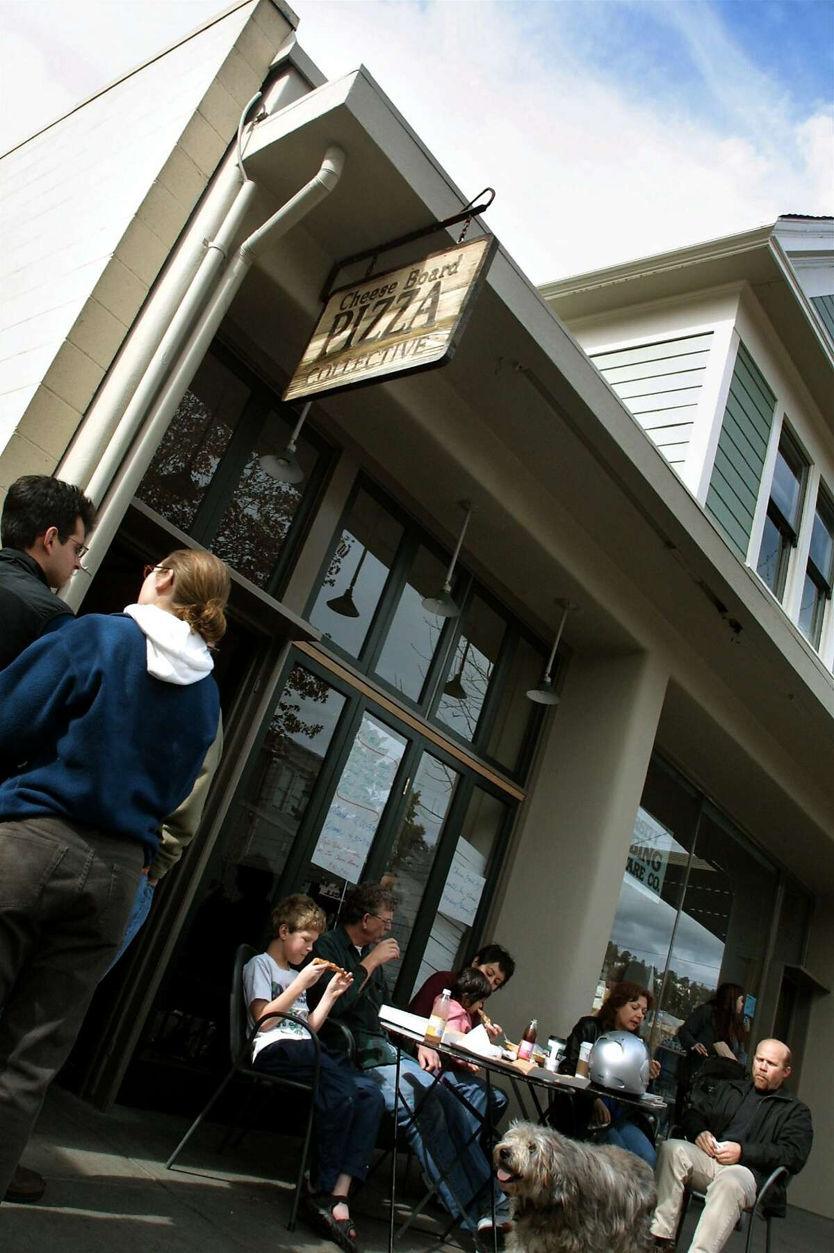 People wait outside for pizza at the Cheese Board Pizza Collective in Berkeley, Calif.