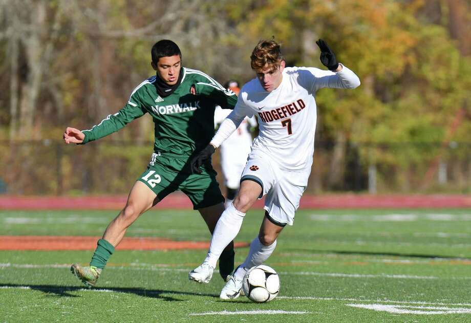 James Siano (7) of the Ridgefield Tigers brings the ball up field defended by Joshua Velez (12) of the Norwalk Bears during the CIAC Class LL Boys Soccer quarter-final round on Friday November 10, 2017 in Ridgefield, Connecticut. Photo: Gregory Vasil / For Hearst Connecticut Media / Connecticut Post Freelance