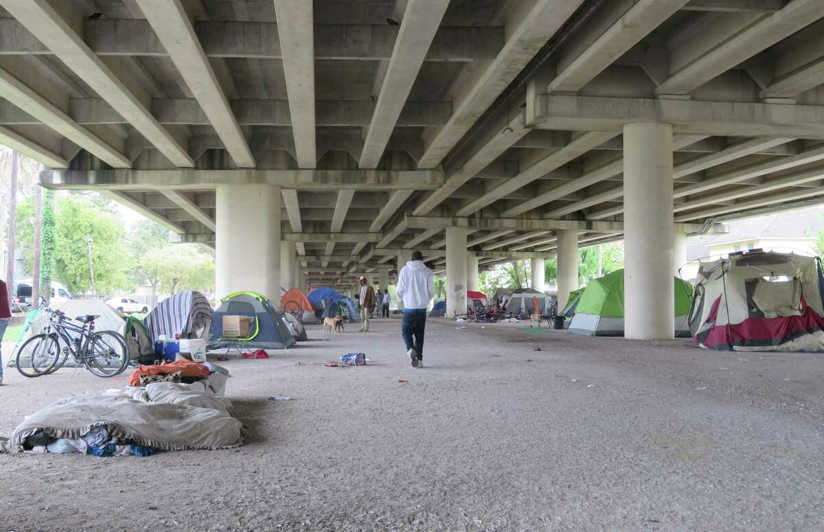 Individuals walked around at a homeless encampmentThursday Nov. 9, 2017 near downtown Houston, Texas. Houston Mayor Sylvester Turner said Thursday such homeless encampments in the city are becoming public safety and health hazards. Turner said the city can't get rid of the encampment because of an ongoing court order that is blocking a city ordinance which bans such sites. The American Civil Liberties Union, which is suing to block the ordinance, says the ordinance is criminalizing homelessness. (AP Photo/Juan A. Lozano)