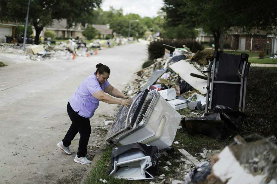 Maria Rocha places debris outside her home in a neighborhood that was flooded by Hurricane Harvey in Beaumont in this  Sept. 26 photo. An additional $90 million approved to help expedite debris removal along Texas' devastated Gulf Coast regions. Photo: David Goldman /Associated Press / Copyright 2017 The Associated Press. All rights reserved.