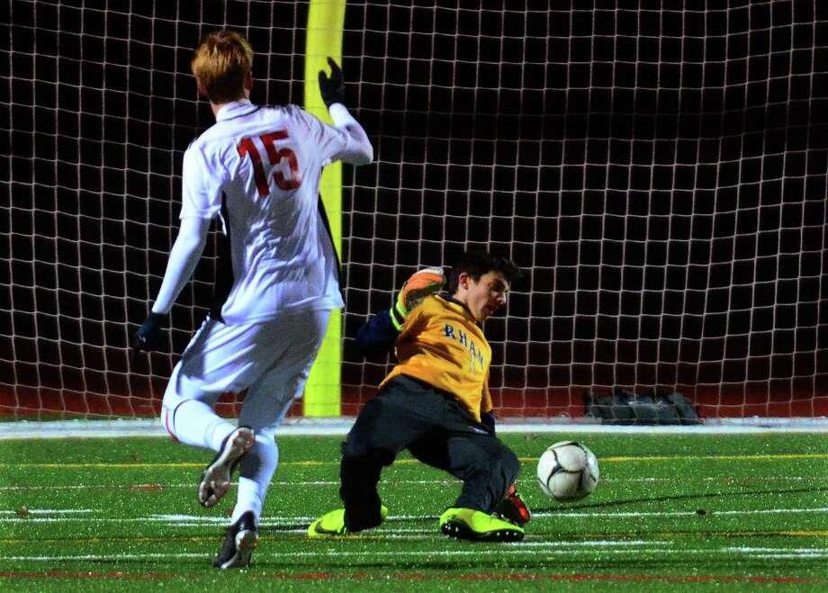 Masuk's Ryan Winkler scores past RHAM goalie Duncan Henderson on Friday in Monroe. Photo: Christian Abraham / Hearst Connecticut Media / Connecticut Post