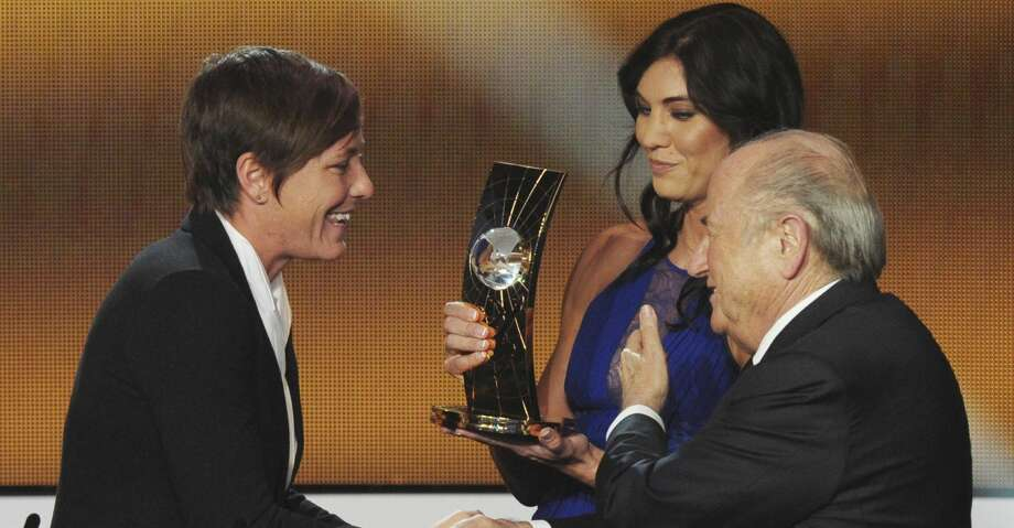 "FILE - In this Jan. 7, 2013, file photo, Abby Wambach, left, of the United States is presented the FIFA Women's World Player of the Year award by Hope Solo, center, goalkeeper of the U.S. team, and FIFA President Sepp Blatter, right, during the FIFA Ballon d'Or Gala held at the Kongresshaus in Zurich, Switzerland. Solo told a Portuguese newspaper that former FIFA President Blatter sexually assaulted her at the ceremony. In an interview published Friday, Nov. 10, 2017, in the newspaper Expresso, Solo said Blatter ""grabbed"" her inappropriately on her rear end shortly before the two appeared onstage at the awards event. (AP Photo/Keystone, Steffen Schmidt, File) Photo: Steffen Schmidt/Associated Press"