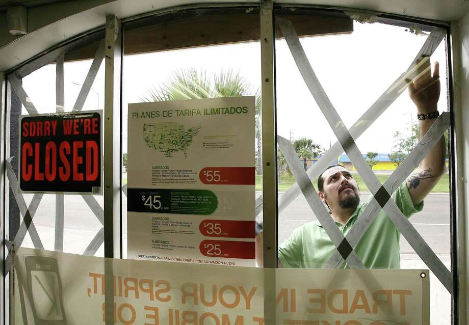 PORT ISABEL, TX - JULY 22 : Raul Valdez tapes the windows of his store ahead of Hurricane Dolly July 22, 2008 in Port Isabel, Texas. Dolly was declared a Category 1 hurricane this afternoon with sustained winds at 75 mph, expected to make landfall in extreme south Texas and northern Mexico around noon tomorrow, forecasters said.  (Photo by Dave Einsel/Getty Images) Photo: Dave Einsel, Stringer / Getty Images / Getty Images North America