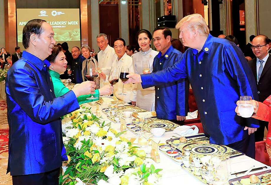 Vietnams President Tran Dai Quang (L) makes a toast with US President Donald Trump (R) at the start of the Asia-Pacific Economic Cooperation (APEC) Summit leaders gala dinner in the central Vietnamese city of Danang on November 10, 2017. World leaders and senior business figures are gathering in the Vietnamese city of Danang this week for the annual 21-member APEC summit. Also pictured are Tran's wife Nguy?n Th? Hi?n (2nd L), Thailand's Prime Minister Prayut Chan-O-Cha (2nd R), his wife Naraporn (3rd R), Taiwan's representative James Soong (4th R) and Singapore's Prime Minister Lee Hsien Loong (5th R). / AFP PHOTO / Vietnam News Agency / STRSTR/AFP/Getty Images ORG XMIT: 1099 Photo: STR / AFP