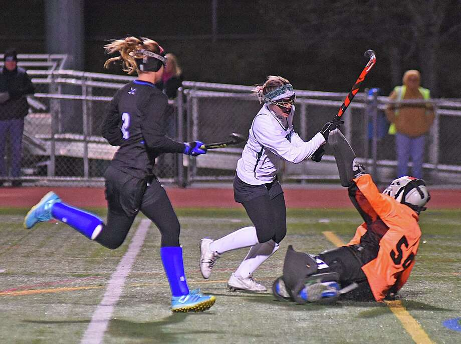 Norwalk's Lily L'Archevesque, center, pushes the ball past Darien goalie Erica Blaze, right, as Blue Wave defender Sally Cassidy races back into the play. L'Archevesque scored on the play, but Darien won 2-1 in overtime. Photo: John Nash / Hearst Connecticut Media / Norwalk Hour