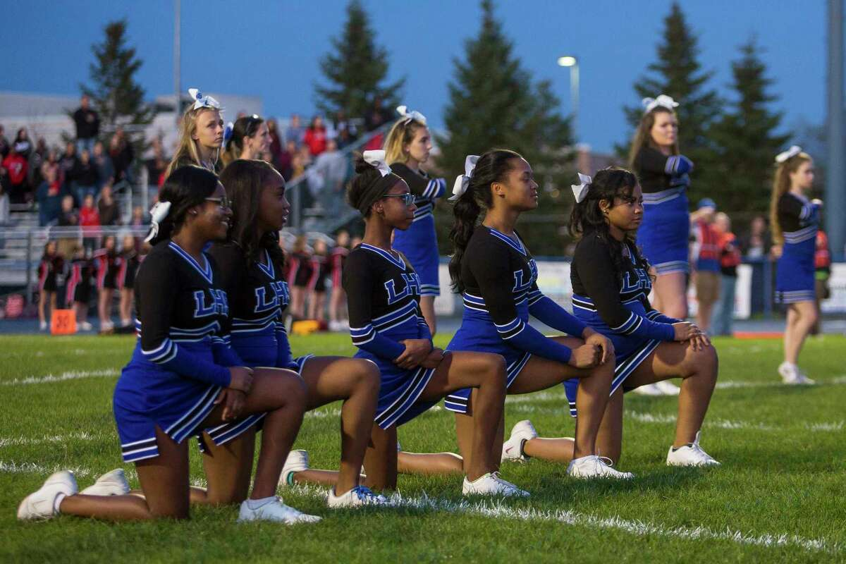 High school cheerleaders in Michigan kneel during the national anthem before a football game Oct. 20, 2017. (Matt Weigand/The Ann Arbor News via AP)