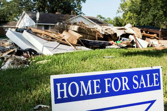 A for sale sign is seen next to a debris pile in the Arbor Oaks neighborhood on Sept. 20, in Houston.