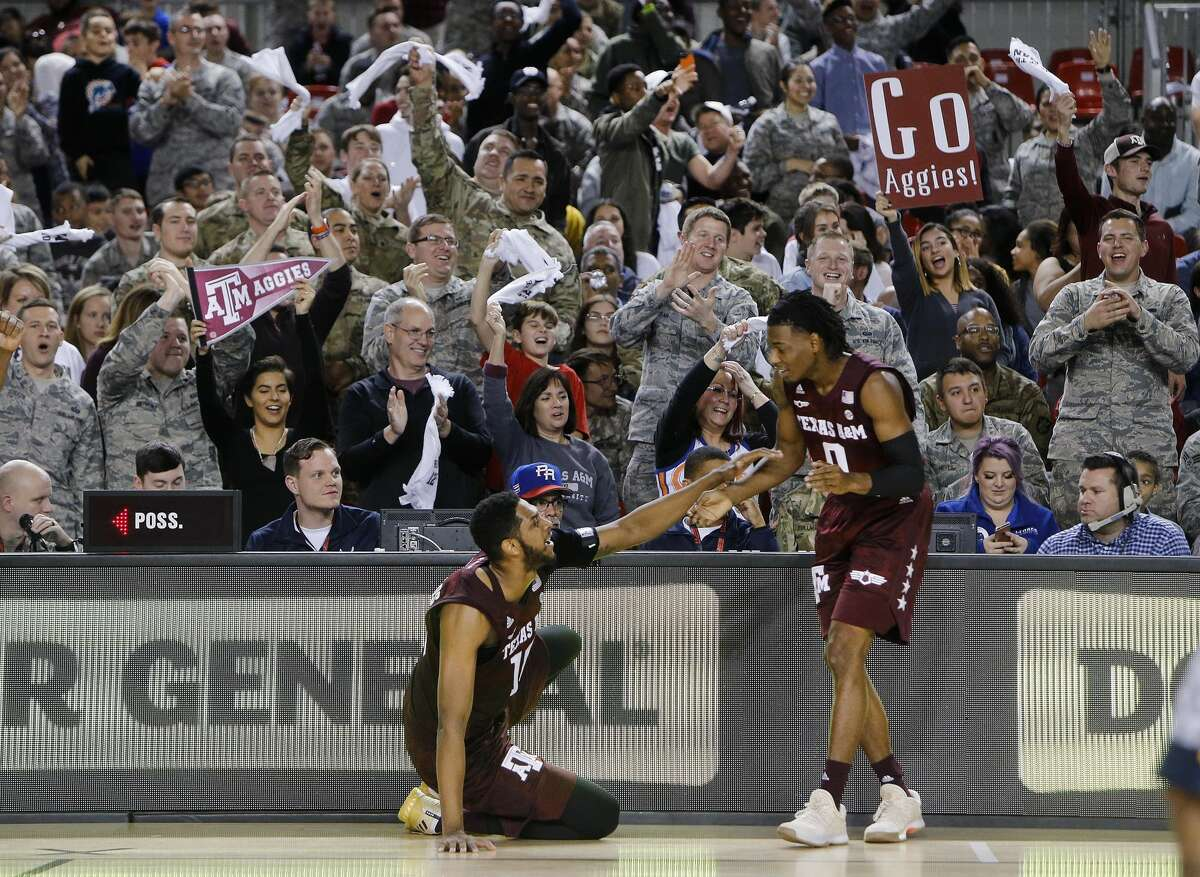 Aggies supporters cheer as two Aggies players sit in front of them during a college basketball match of the Armed Forces Classic between Texas A&M Aggies and West Virginia Mountaineers on the US Air Base in Ramstein, Germany, Saturday, Nov. 11, 2017. (AP Photo/Michael Probst)