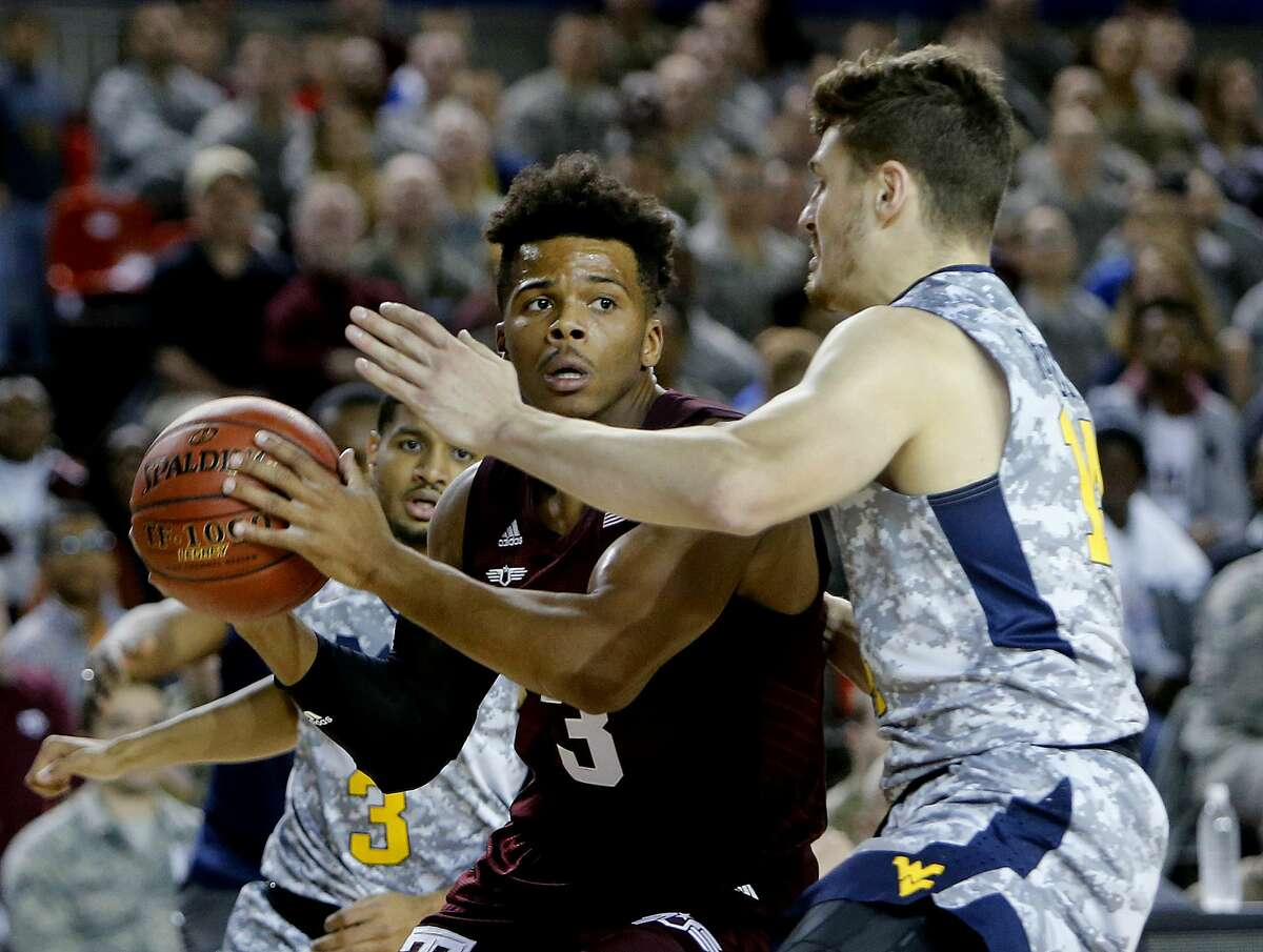 Texas' Admon Gilder, left, looks to move past West Virginia's Chase Harler during a college basketball match of the Armed Forces Classic on the U.S. Air Base in Ramstein, Germany, Saturday, Nov. 11, 2017. (AP Photo/Michael Probst)