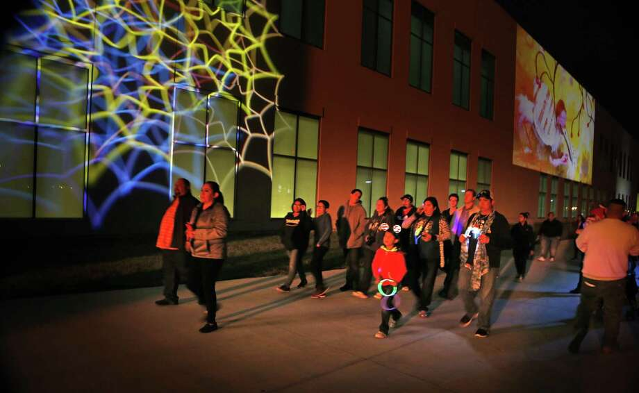 People walk by the video screened on walls at Hemisfair.Coverage of Luminaria, which marks its 10th anniversary with a return to Hemisfair on Friday, November 10, 2017. Photo: Photos By Ron Cortes / For The San Antonio Express-News