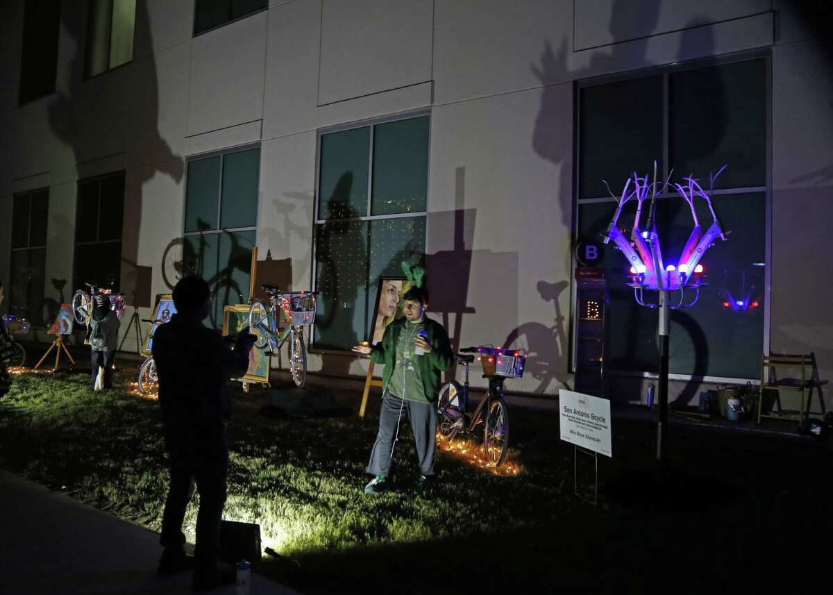 Adrian Quirks has his photo taken at the Share shares art exhibit Coverage of Luminaria, which marks its 10th anniversary with a return to Hemisfair on Friday, November 10, 2017.