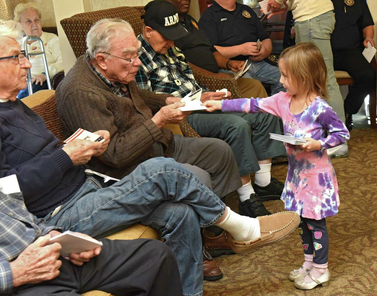 Sienna Scavio, 4, of Guilderland hands Air Force veteran Ken Marriott, 93, a card at the Atria Crossgate assistant living facility on Friday, Nov. 10, 2017 in Albany, N.Y. A group of children who are patients of local orthodontist Dr. Sergey Berenshteyn marked Veterans Day by presenting hundreds of thank you cards to veterans. (Lori Van Buren / Times Union)'