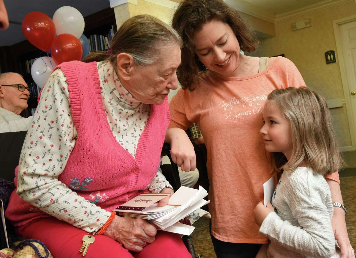 Veteran Navy nurse Grace Roznowski, 97, gets a card from Rosie Surman, 4, of Guilderland with her mom Cheryl Surman next to her at the Atria Crossgate assistant living facility on Friday, Nov. 10, 2017 in Albany, N.Y. A group of children who are patients of local orthodontist Dr. Sergey Berenshteyn marked Veterans Day by presenting hundreds of thank you cards to veterans. (Lori Van Buren / Times Union)'