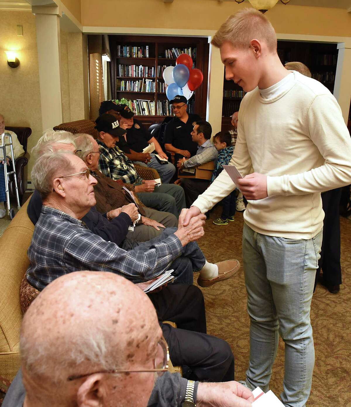 Josh Janack, 15, of Glenville gives a card to veteran Neal Martinis, 89, at the Atria Crossgate assistant living facility on Friday, Nov. 10, 2017 in Albany, N.Y. A group of children who are patients of local orthodontist Dr. Sergey Berenshteyn marked Veterans Day by presenting hundreds of thank you cards to veterans. (Lori Van Buren / Times Union)'