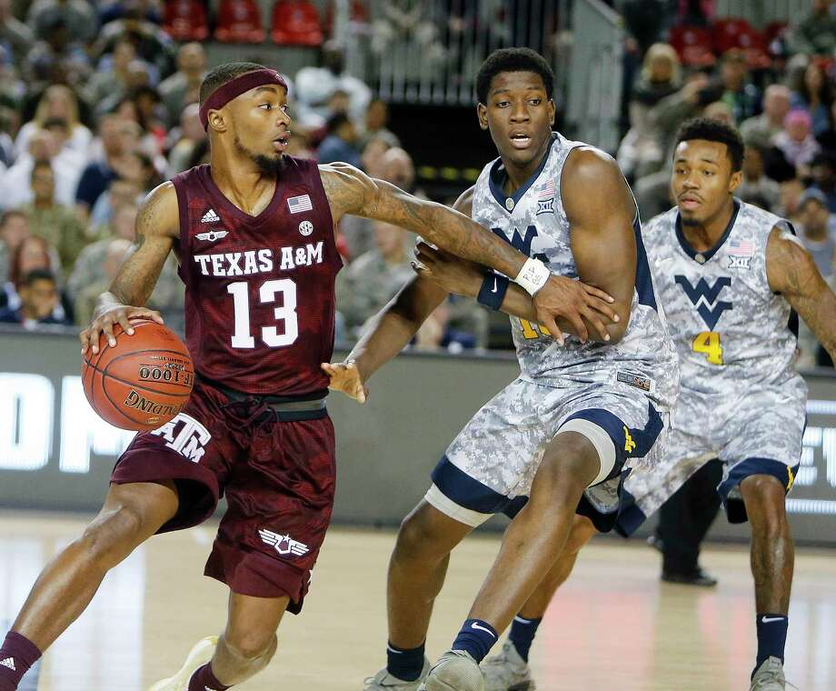 Aggies' Duane Wilson, left, and West Virginia's Lamont West challenge for the ball during a college basketball match of the Armed Forces Classic between Texas A&M Aggies and West Virginia Mountaineers on the US Air Base in Ramstein, Germany, Saturday, Nov. 11, 2017. (AP Photo/Michael Probst) Photo: Michael Probst, Associated Press / Copyright 2017 The Associated Press. All rights reserved.