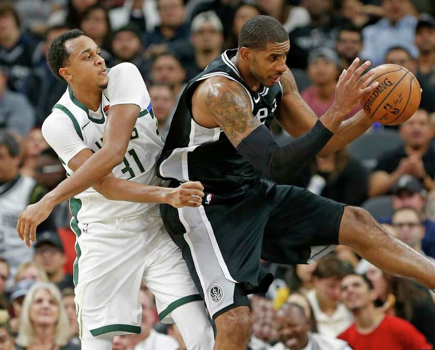 Milwaukee Bucks John Henson and San Antonio Spurs' LaMarcus Aldridge grab for a rebound during first half action Friday Nov. 10, 2017 at the AT&T Center.