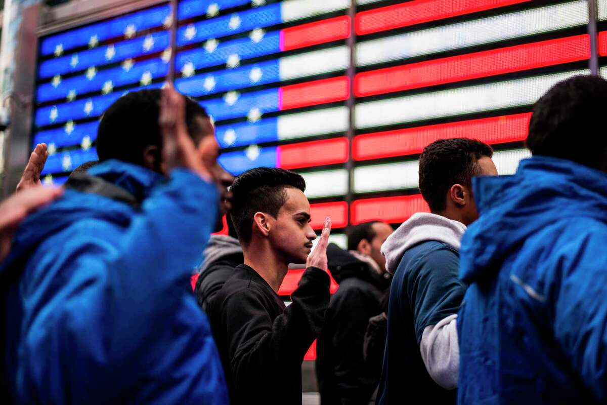 New recruits raise their hands as they take an oath outside the renovated Times Square Military Recruiting Station in New York on November 10, 2017. / AFP PHOTO / Jewel SAMADJEWEL SAMAD/AFP/Getty Images