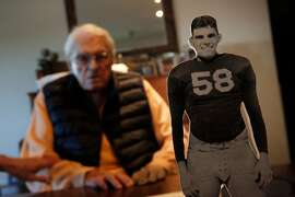 Robert Wilhelm sits next to a mounted cut out of him in his uniform from when he played with the California Golden Bears at his home on Tuesday, November 7,  2017 in San Rafael, Calif. Robert Wilhelm is the last living member of the California Golden Bears team from the 1938 Rose Bowl.