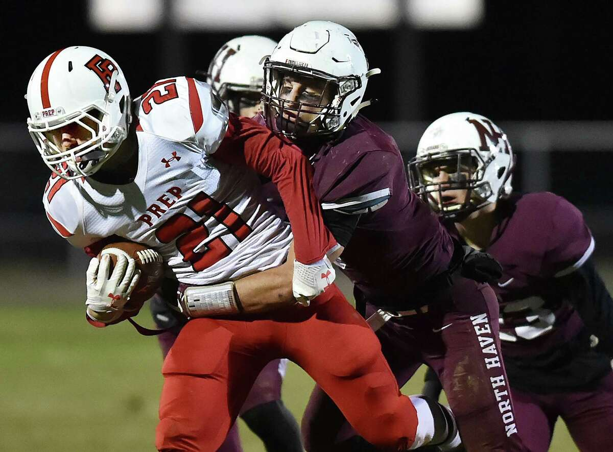 North Haven's Mark Montano tackles Fairfield Prep's Thomas Walton on Friday at Vanacore Field in North Haven.