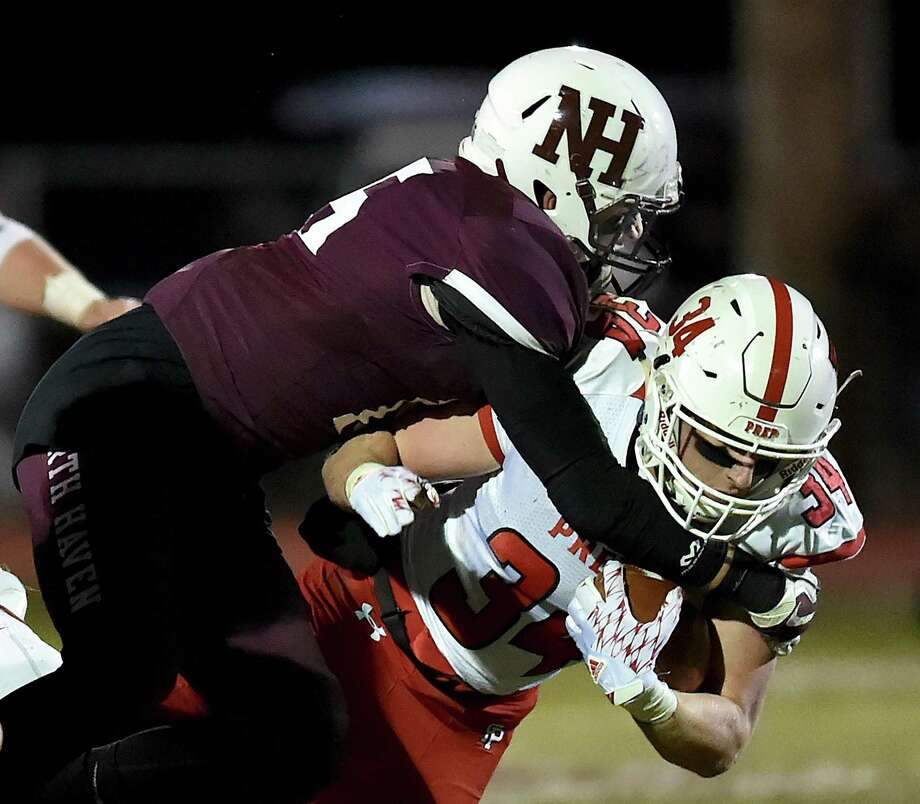 North Haven's Steven Erbe tackles Fairfield Prep's Justin Keith on Friday at Vanacore Field in North Haven. Photo: Catherine Avalone / Hearst Connecticut Media / New Haven Register