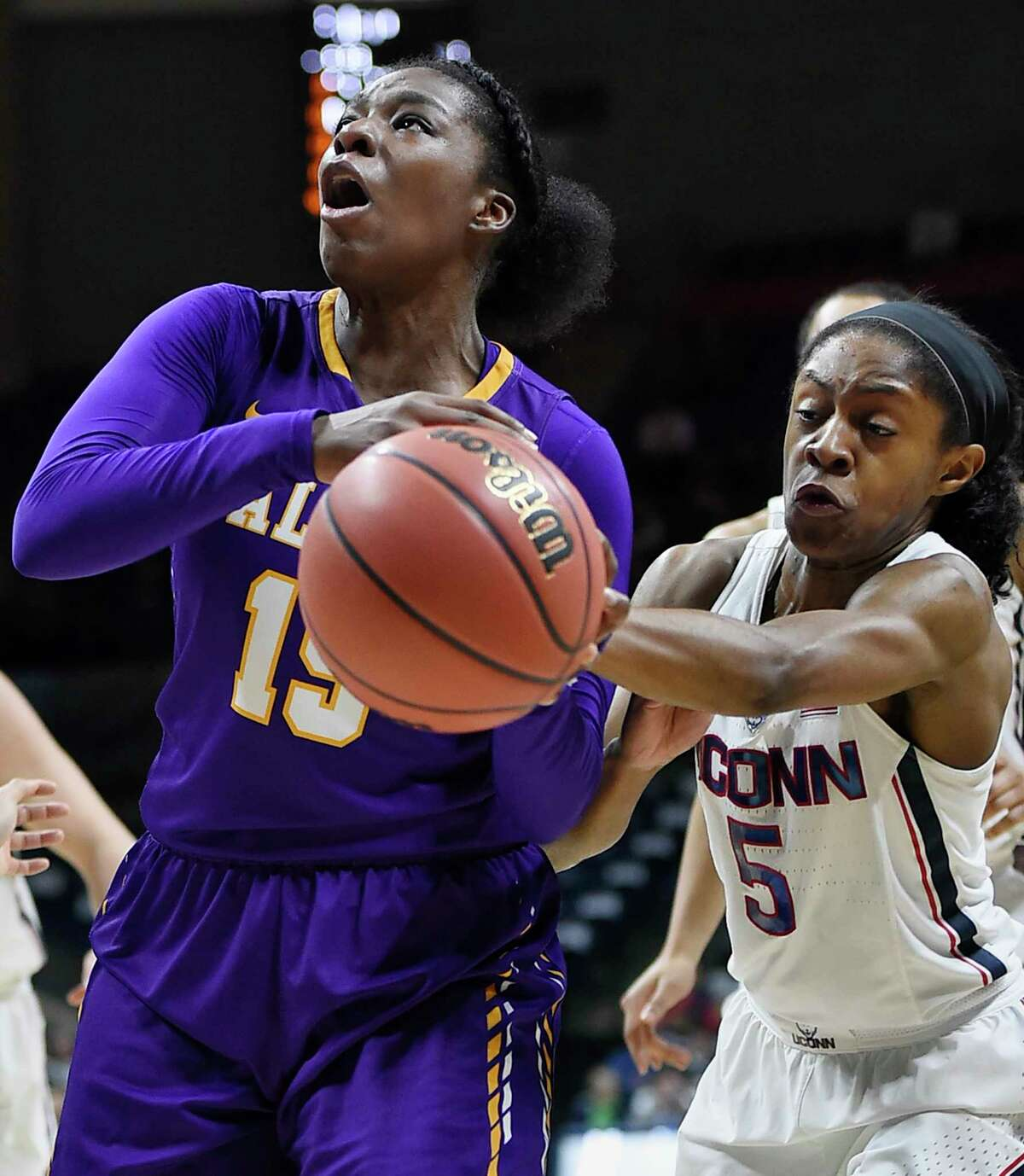 Connecticut's Crystal Dangerfield, right, reaches for the ball as Albany's Jessica Féquiere, left, shoots during the first half of a first round round of a women's college basketball game in the NCAA Tournament, Saturday, March 18, 2017, in Storrs, Conn. (AP Photo/Jessica Hill) ORG XMIT: CTJH107