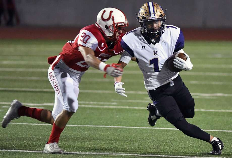 Midland High's Mikey Galindo (1) runs following a pass reception as Odessa High's Charles McClure (20) pursues during the first quarter of their district football game Friday at Ratliff Stadium. Photo: Mark Sterkel|Odessa American