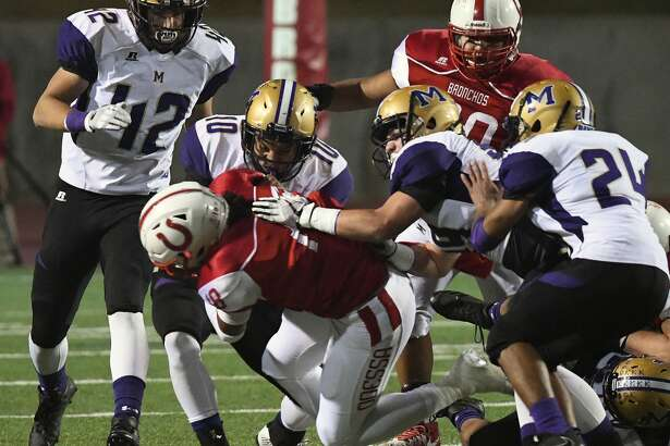 Midland High defenders Caedan McDonald (10), Elijah Turner (12), Tony Zarate (24) and Stetson Abney (99) swarm to bring down Odessa High running back Senjun McGarity (18) during their district football game Friday at Ratliff Stadium.
