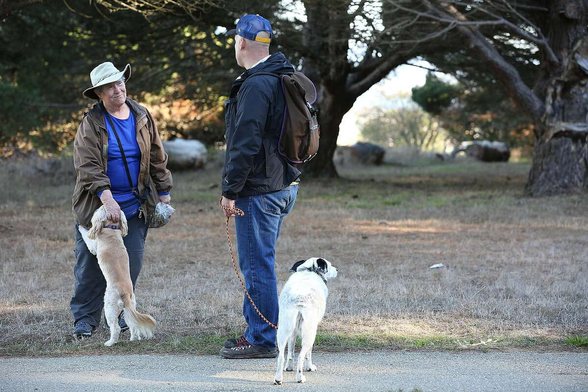 Alex Aldrich stops to talk about the park trails with Joan Fanning, walking Peaches, at McLaren Park.
