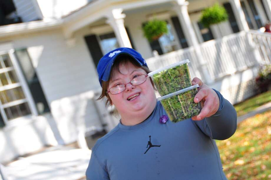 Susie, an Abilis volunteer, with microgreens grown organically for Glenville Greens — a microgreen and specialty herb farm that delivers the produce to area restaurants. Photo: Contributed