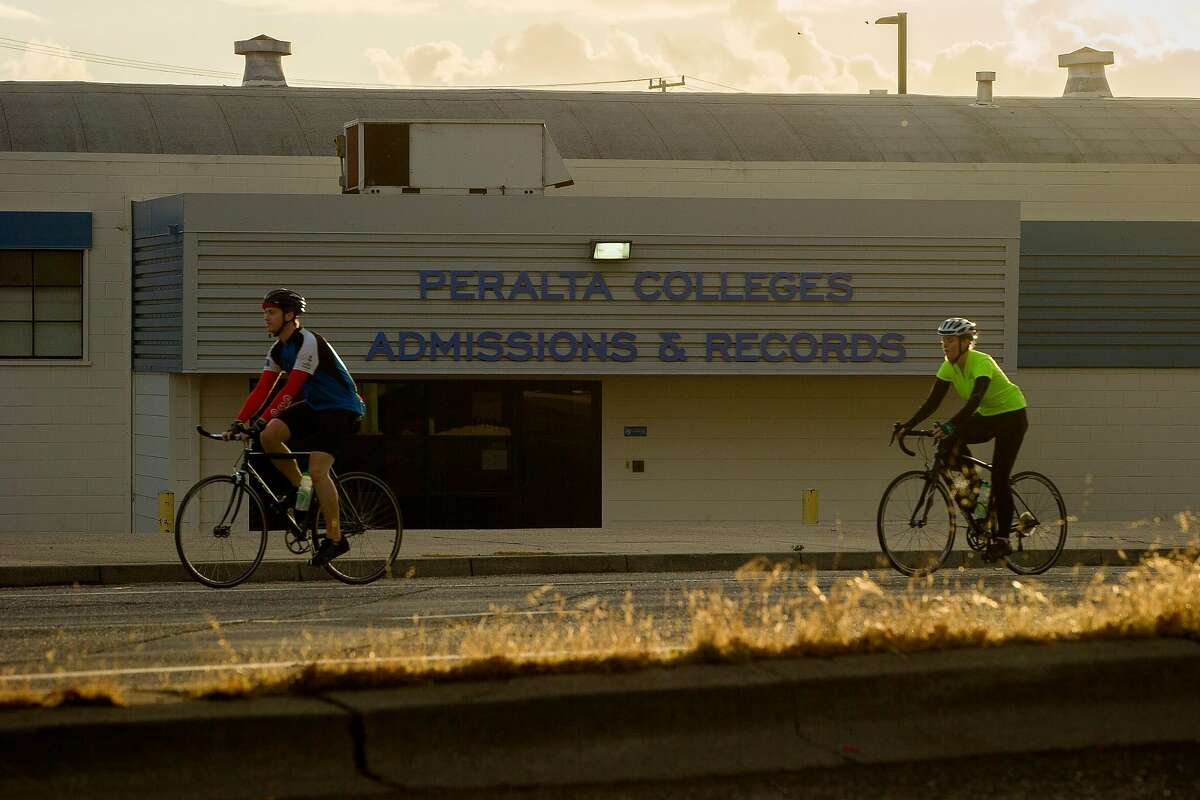 Bicyclists ride past the Peralta Colleges headquarters on Friday, Nov. 10, 2017, in Oakland, Calif. The Oakland A's are proposing a new stadium at the Peralta Community College District headquarters near Laney College.