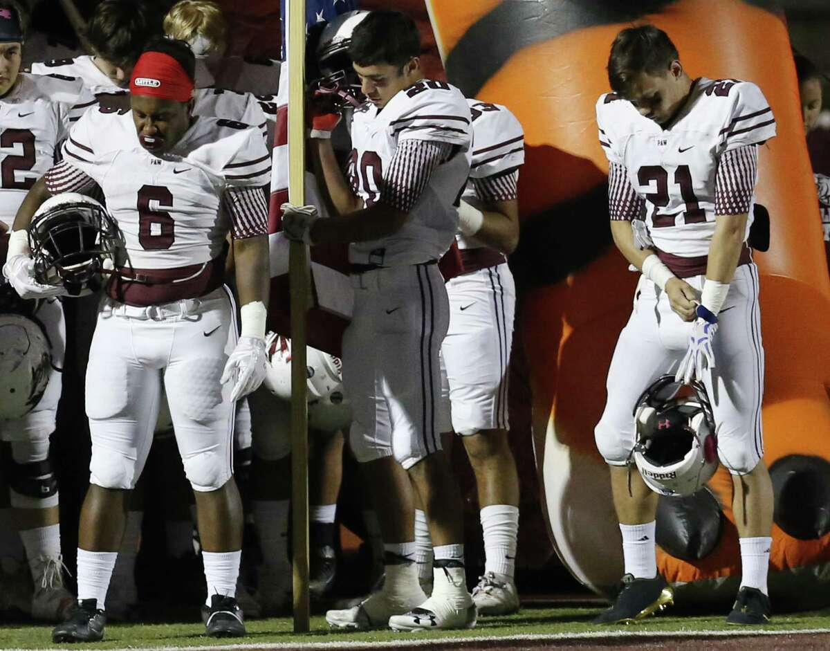 Floresville's Salih Williams (06), Nathan Pollok (20) and Kane Numera (21) bow their heads in prayer before the game against Southside during their District 29-5A title game in Floresville on Friday, Nov. 10, 2017. (Kin Man Hui/San Antonio Express-News)