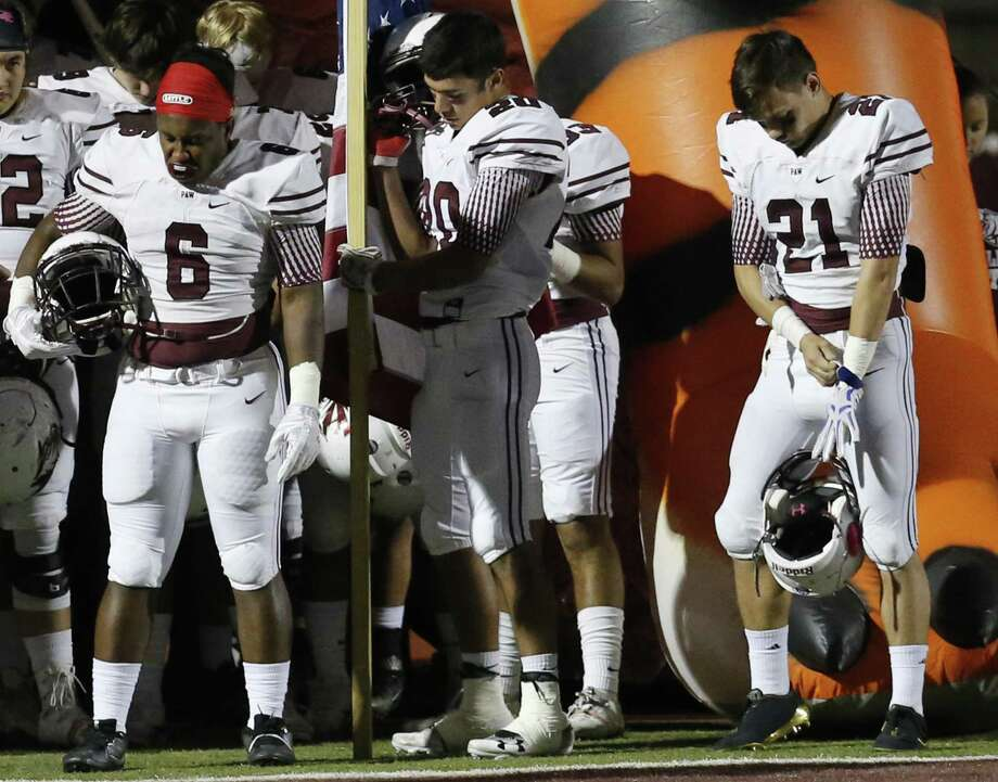 Floresville's Salih Williams (06), Nathan Pollok (20) and Kane Numera (21) bow their heads in prayer before the game against Southside during their District 29-5A title game in Floresville on Friday, Nov. 10, 2017. (Kin Man Hui/San Antonio Express-News) Photo: Kin Man Hui, Staff / San Antonio Express-News / ©2017 San Antonio Express-News
