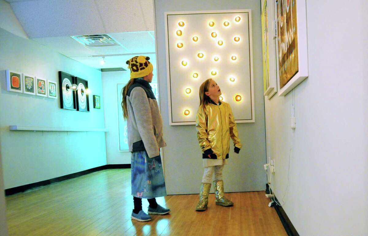 Charlotte Joergensen, 10, and her little sister Isobel, 8, browse artwork created by Cris Dam during the 9th Annual Bridgeport Art Trail Arcade Night, the kick-off of a two-day open studio experience on Friday.