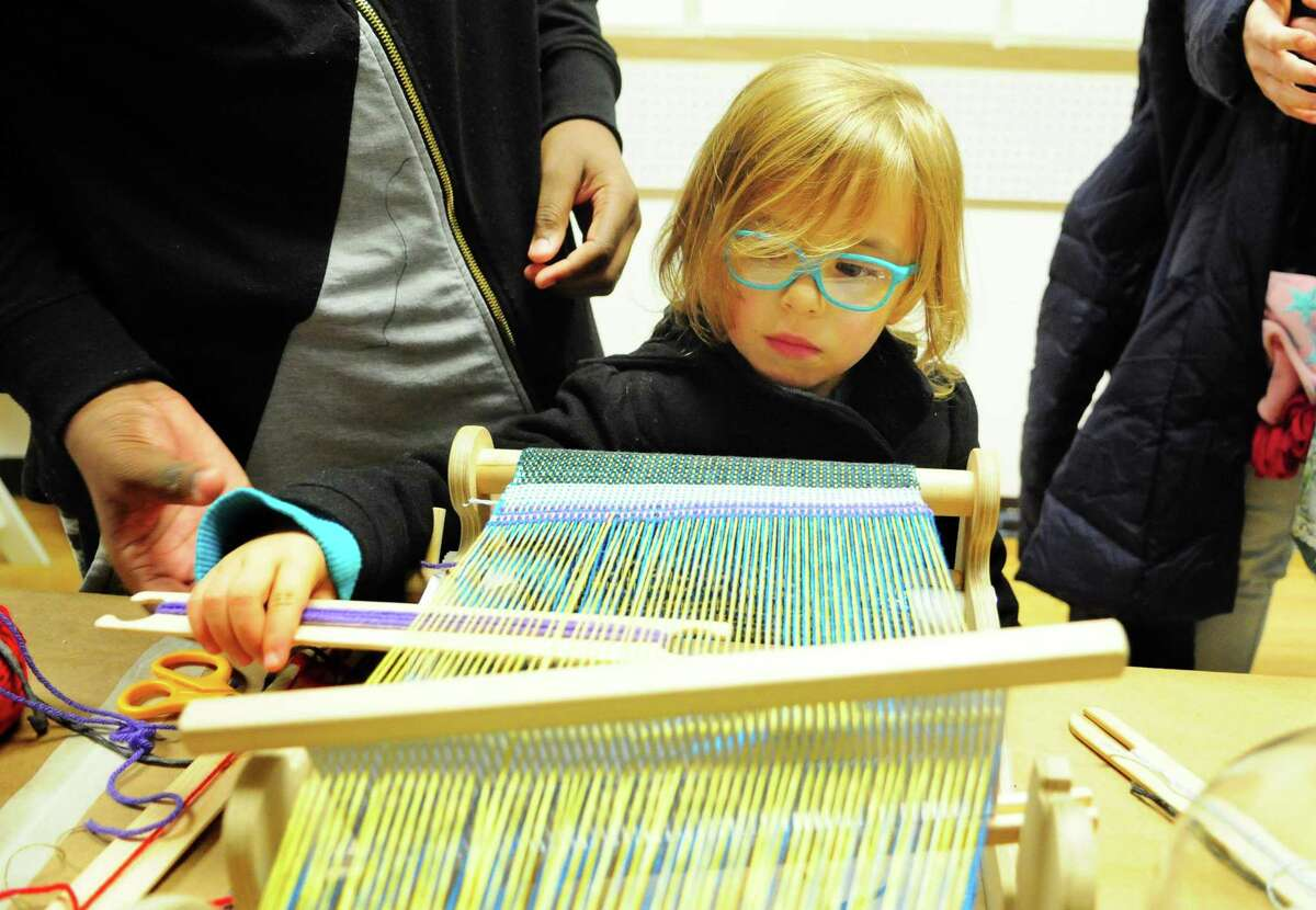 Sylvia Brion, 4, takes part in a weaving session at Ruben Marroquin's textile art studio during Arcade Night on Friday. The event was part of the 9th Annual Bridgeport Art Trail.