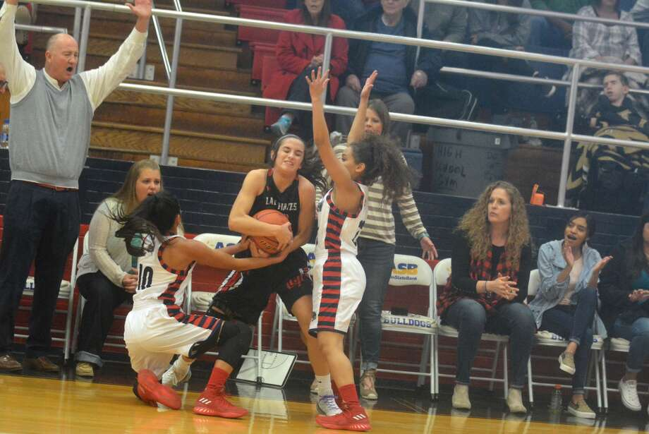 Plainview girls' basketball coach Danny Wrenn, left, raises his hands as Lady Bulldog players Kristan Rincon, 10, and Osen Ellis, right, try to get the ball away from a Lubbock Cooper player during a game at the Plainview High School gym Saturday. Photo: Skip Leon/Plainview Herald