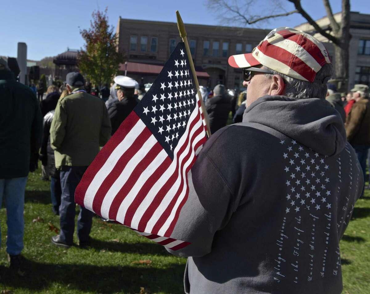 Mark E. Rosato, of New Milford, holds a flag and listens to a speaker during the annual New Milford Veterans Day Ceremony, held on 11/11 at 11am on the New Milford Town Green. Saturday morning, November 11, 2017, in New Milford, Conn. Rosato father Louis A. Rosato was a U.S. Army WWII veteran who served in Europe.