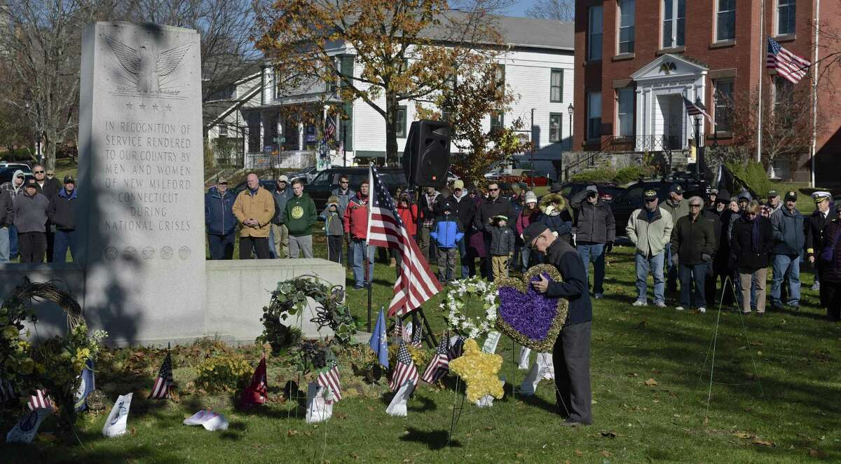 World War II veteran Paul Hulton, U.S. Army, of New Milford, places a Purple Heart wreath, at the base of the All Wars Memorial the annual New Milford Veterans Day Ceremony, held on 11/11 at 11am on the New Milford Town Green. Saturday morning, November 11, 2017, in New Milford, Conn.