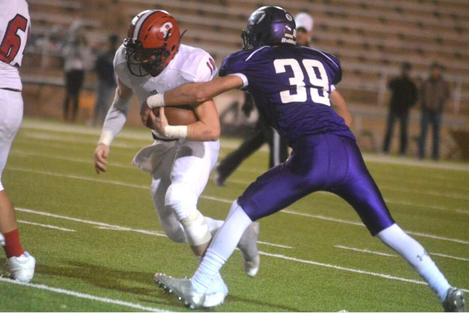 Plainview quarterback Carson Hauk, 10, runs for yardage as Canyon's Brent Stockstill, 39, tries to rip the ball away from him during a District 3-5A football game in Canyon Friday night. The Bulldogs clinched the final playoff spot from the district with a 38-28 victory. Photo: Skip Leon/Plainview Herald