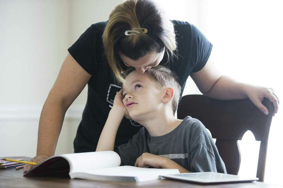 Heidi Walker kisses her son Roanin Walker, 7, during a pause from studying math at their home in Kingwood in this 2016 photo. Roanin has been diagnosed with attention deficit disorder, anxiety and sensory processing disorder. His parents decided to pull him out of school to homeschool him after he was denied special education help. A 2016 Houston Chronicle investigation found that tens of thousands of students with disabilities were denied access to services because of the de-facto cap. TEA eliminated the policy in November 2016. Photo: Houston Chronicle File Photo / © 2016 Houston Chronicle