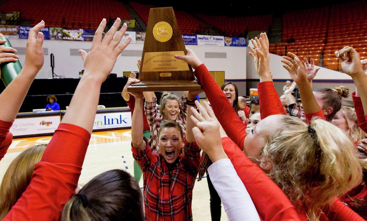 The Woodlands head coach Terri Wade raises the Region II-6A championship trophy after the Lady Highlanders defeated College Park 3-1 at Johnson Coliseum, Saturday, Nov. 11, 2017, in Huntsville.